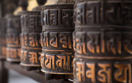 Buddhist obsolete prayer wheels in row with artistic shallow DOF in Nepal Stock Photo
