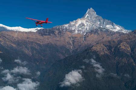 Ultralight plane flies over Pokhara and Machapuchare in Annapurna region, Nepal