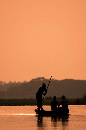 Men in a boat on a river silhouette with sunset light
