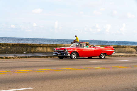 Red retro taxi car with tourists in Havana, Cuba. Captured on Malecon roadway in spring 2018 Editorial