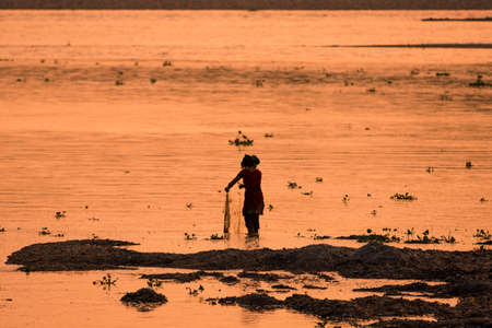 Asian Woman fishing in the river. silhouette at sunset. Village life in Asia