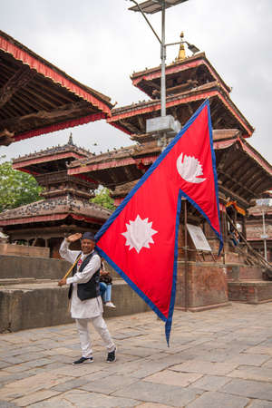 Man holding Nepalese Flag on Durbar square in Kathmandu, Nepal. Captured in May 2018