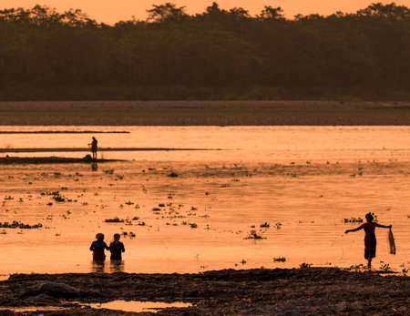 Asian Women fishing in the river. silhouette at sunset. Village life in Asia