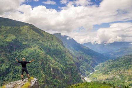 Man standing on top of the hill in Himalayas. Achievement and success. Trekking in Nepal