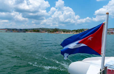 Cuba flag waving on boat at sea near Cuban coastline. Tourism in Cuba Standard-Bild