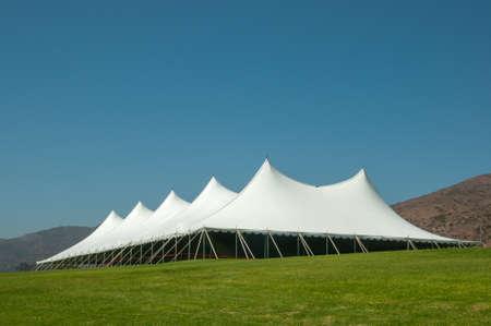 Grande tente blanche pour événements dans un domaine verdoyant Banque d'images
