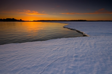 frozen waves: Sunset reflection and snowy ice