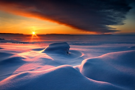 Snowy seascape with dark cloud and rising sun photo