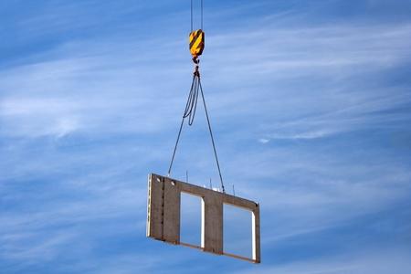 Constructon site crane is lifting a precast concrete wall panel