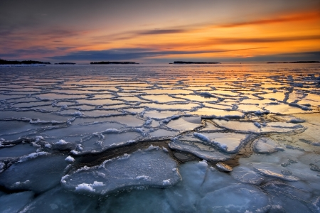 Morning dawn with frozen ice floats in sea coast photo