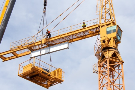 Setting up a tower crane in the construction site Standard-Bild