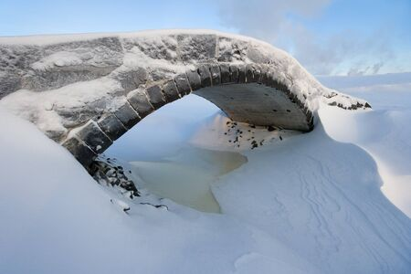 frigid: Small old stone bridge in snowy winter day