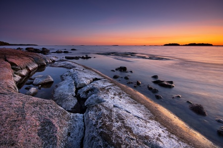 Late evening seascape with salt colored rock photo