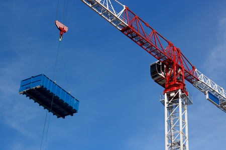 Tower crane is lifting truck dumpster on the sky Stock Photo - 14979526