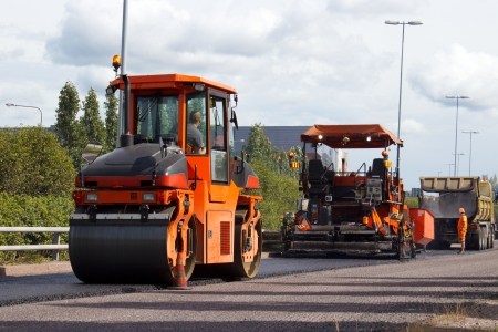 road worker: Asphalt roller and pavement machine in use