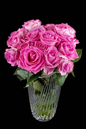 roses in vase: Pink rose flowers in glass vase, isolated on black