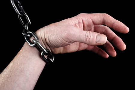 shackle: Male hand in shackles, black background