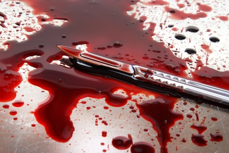 Surgeon knife on steel autopsy table with blood