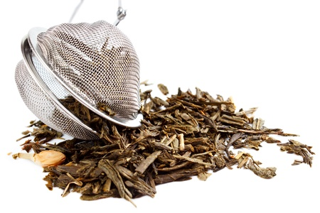 tea strainer: Tea herbs with strainer , isolated on white