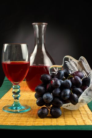 carafe: Grapes with glass of red wine and carafe on place mat
