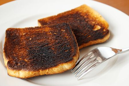 burnt toast: Burnt toast on white plate with fork