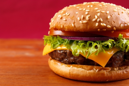 cheese burgers: Hamburger closeup on red background Stock Photo