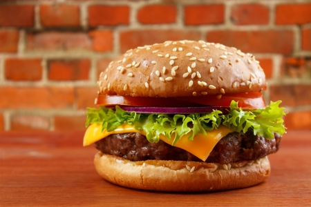 Hamburger on table, red brick wall background