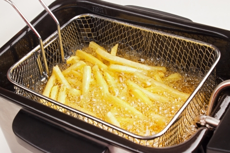 Closeup of french fries in hot fat in a deep fryer Stock Photo