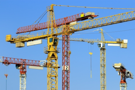 Many tower cranes in construction site photo