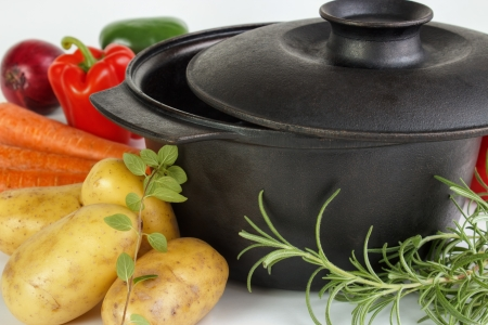 cast iron: Fresh vegetables and herbs with cast iron pot  Stock Photo