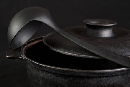 low light: Cast iron cauldron with scoop in low light