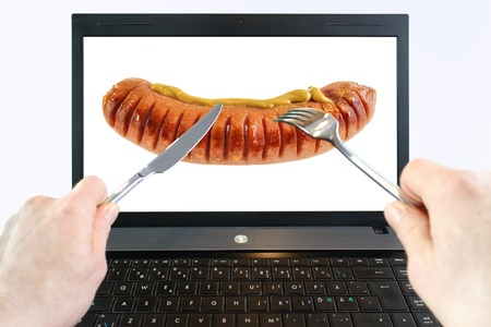 Man is eating virtual food from laptop screen