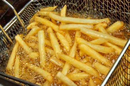 fryer: French fries in a deep fryer closeup