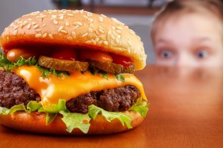 Hongerige jonge jongen is staren rundvlees hamburger op tafel Stockfoto