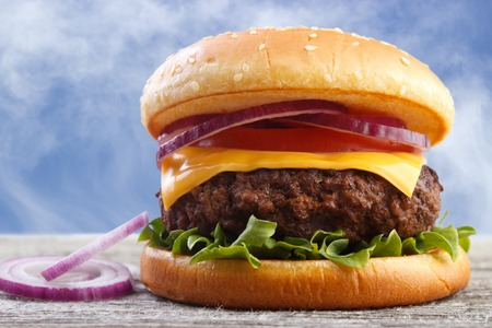 Fresh burger with red onions on wooden board photo