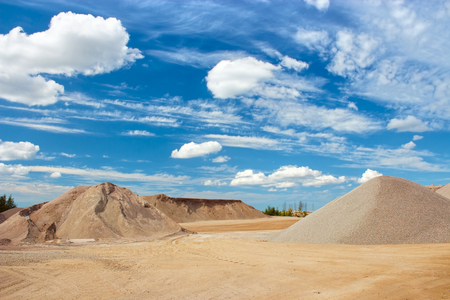 costruction: Sand and gravel quarry site with cloudy blue sky Stock Photo