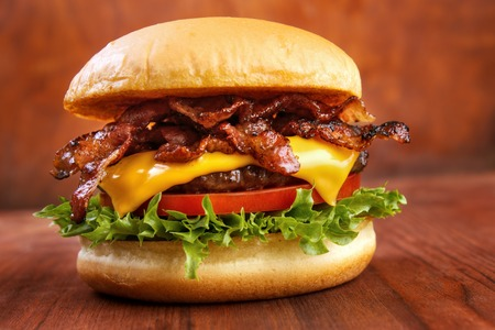 Bacon burger with beef patty on red wooden table Imagens