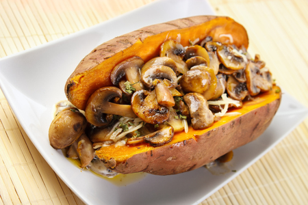 Oven cooked sweet potato , filled with mushroom sauce and roasted champignons