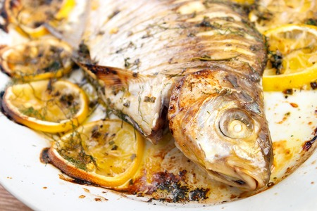 Oven cooked fish with lemon and herbs on dish closeup Standard-Bild