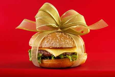 Gift wrapped hamburger , conceptual food image with red baclground Standard-Bild - 107305609