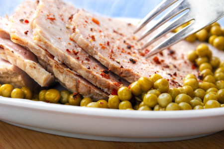 Oven roasted and sliced ham with peas on dish with fork Standard-Bild - 107305610