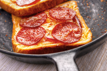 Hot sandwiches with pepperoni and cheese on frying pan