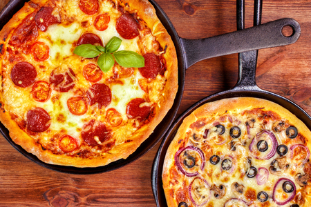 Two fresh pan pizzas on iron skillets , wooden background , top view Standard-Bild - 107305629