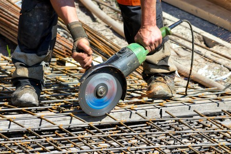 Cutting steel with angle grinder in reinforcing iron site Standard-Bild - 107305631