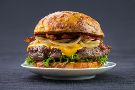 Cheeseburger with bacon and cooked onion on plate , toasted cheese bun Standard-Bild - 107346246