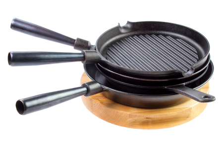 Stack of different cast iron skillets on wooden cutting board, isolated on white background Standard-Bild - 107346247