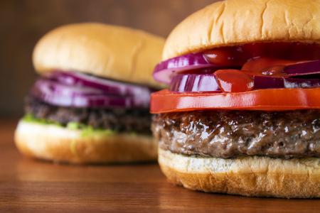 Burgers closeup on wooden table , shallow DOF Standard-Bild - 107346252