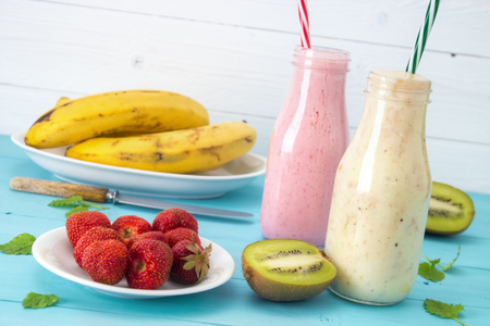 Two different sweet smoothies with fruits on turquoise wooden table Standard-Bild - 107346272