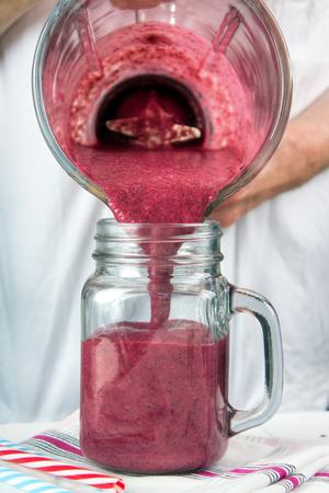 Pouring blended red fruit smoothie to glass mason jar Standard-Bild - 107346270