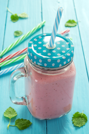 Sweet strawberry smoothie with straws in mason jar on rustic painted table, shallow DOF , focus on lid Standard-Bild - 107346281